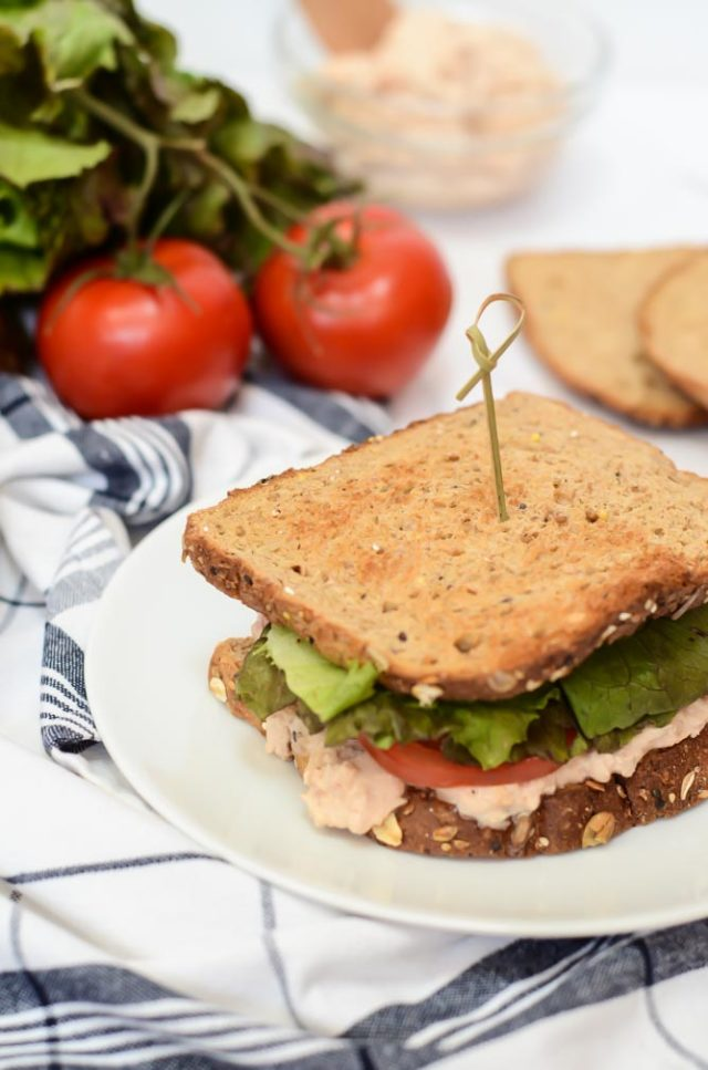 A Quick-and-Healthy Tuna Salad Sandwich held together with a toothpick with lettuce, tomatoes and slices of bread in the background.