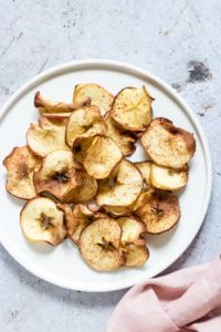 An overhead shot of a plate of Air Fryer Apple Chips - a fun snack for babies and toddlers!