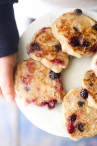 Hands holding a plate of Banana and Blueberry Fritters - a great finger food for babies and toddlers!