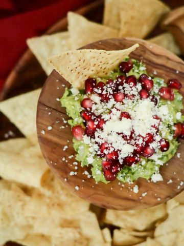 An overhead shot of Festive Guacamole in a bed of tortilla chips.