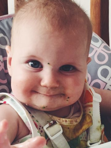 A baby with broccoli all over her face to help showcase the best vegetable preparations for baby-led weaning.