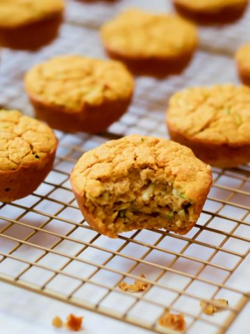 A rack of cooling Sweet Potato Zucchini Muffins shows one with a bite out of it. Vegetable-packed muffins are a great food for 18-month-olds.