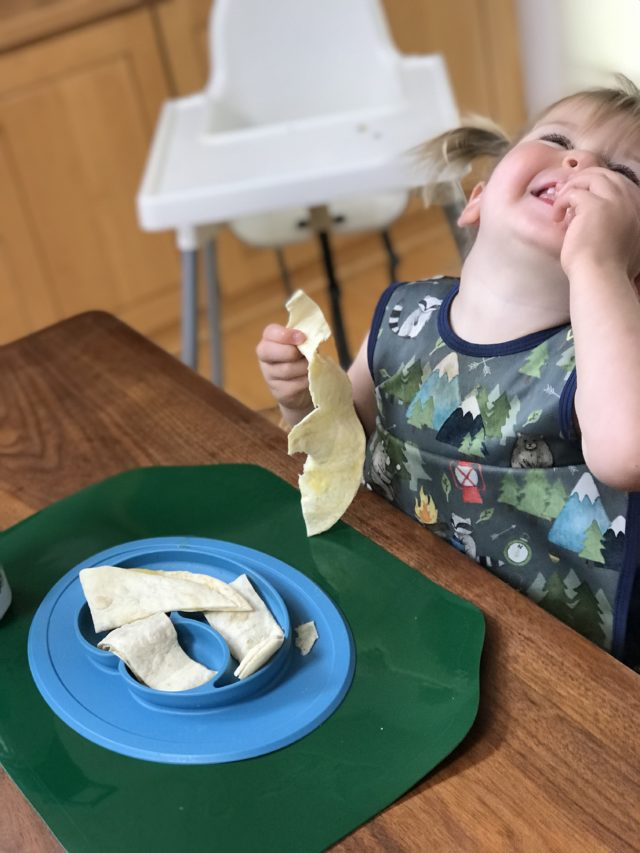 A toddler enjoying a quesadilla. Quesadillas are another great food for 18-month-olds, especially when they have hidden veggies!