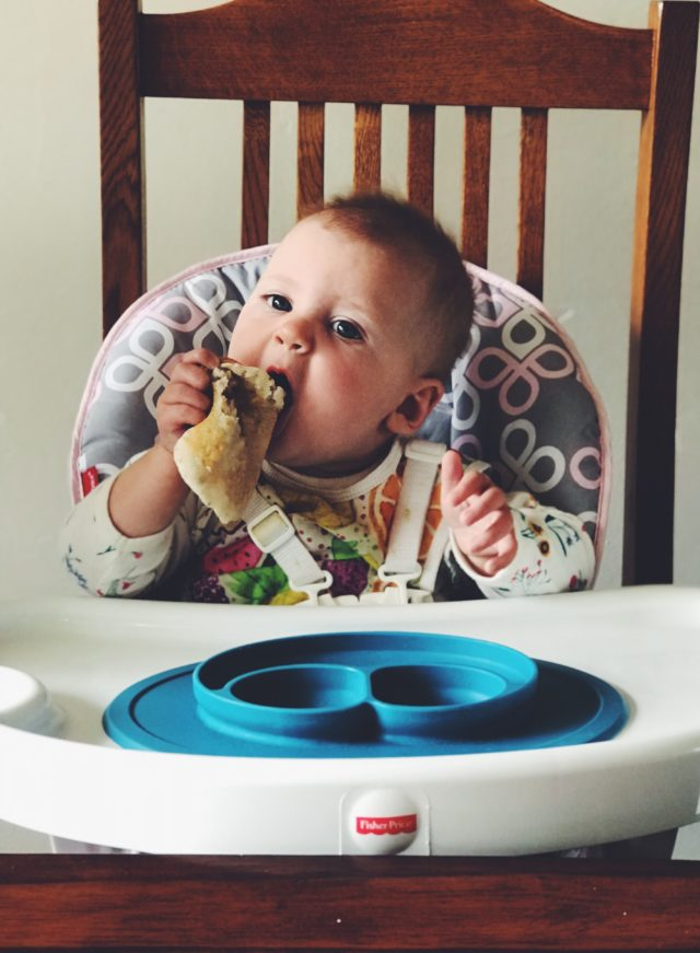 A young baby in her highchair feeding herself a giant pancake.
