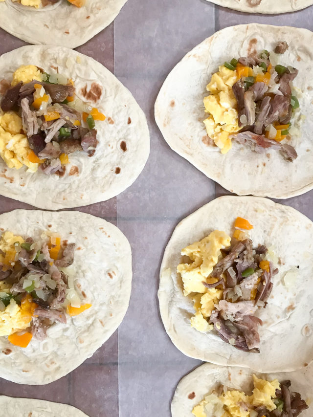 Tortillas lined up and filled with eggs, vegetables and shredded meat to make breakfast enchiladas.