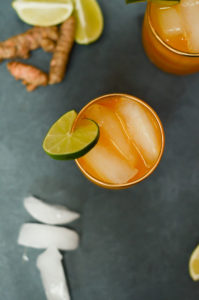 An overhead shot of a glass of tasty Pineapple Turmeric Ginger Elixir, surrounded by ice cubes and fresh ginger root.
