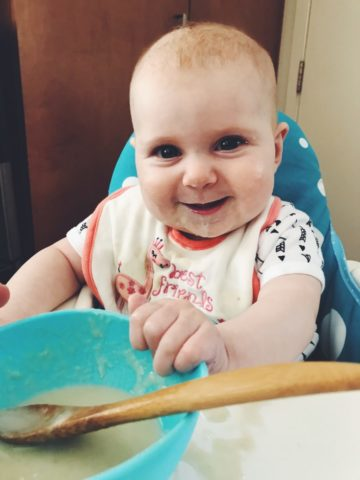 A baby enjoying her first taste of solid food in her highchair.