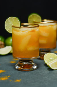 Two glasses of Pineapple Turmeric Ginger Elixir surrounded by limes.