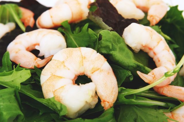 A pile of cooked shrimp on top of a bed of greens. Shrimp is a great food for 10-month-olds as long as they're not allergic!