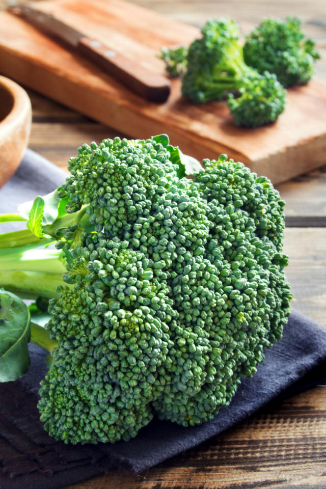 A head of broccoli with some chopped florets in the background.