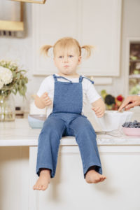 A toddler sitting on a kitchen counter eating blueberries with a quizzical look on her face.