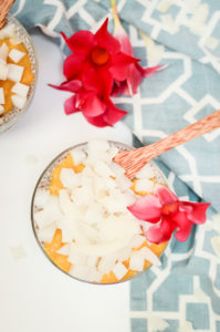 An overhead shot of a wooden spoon resting in a dish of coconut chia pudding.