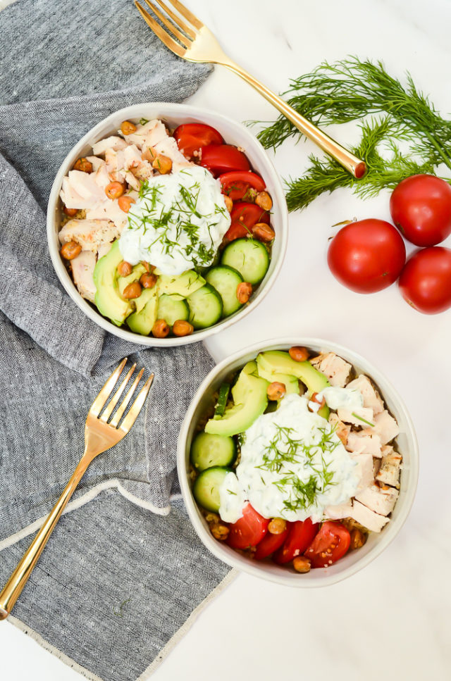 An overhead shot of two healthy Mediterranean Bowls flanked by gold forks, fresh tomatoes and dill.