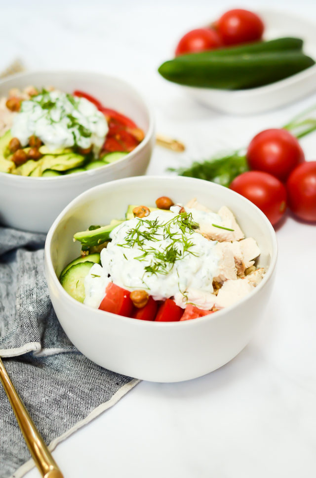 Two Mediterranean Bowls surrounded by fresh tomatoes, dill and cucumber.
