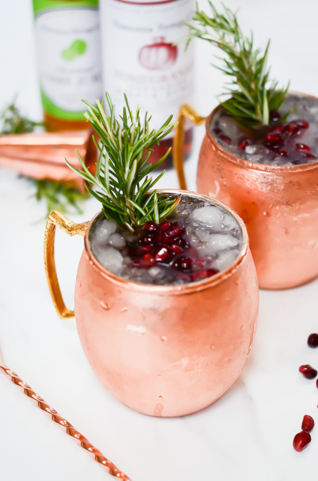 A frosty Pomegranate Mule garnished with fresh pomegranate seeds and rosemary sprigs.