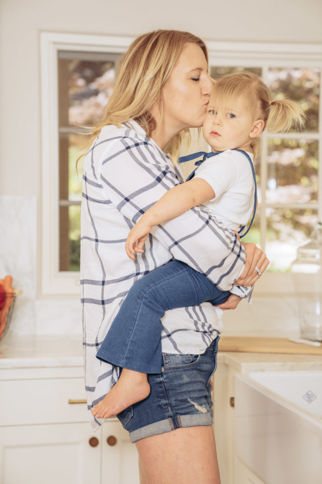 A mama holding her toddler in the kitchen and giving her a big kiss.