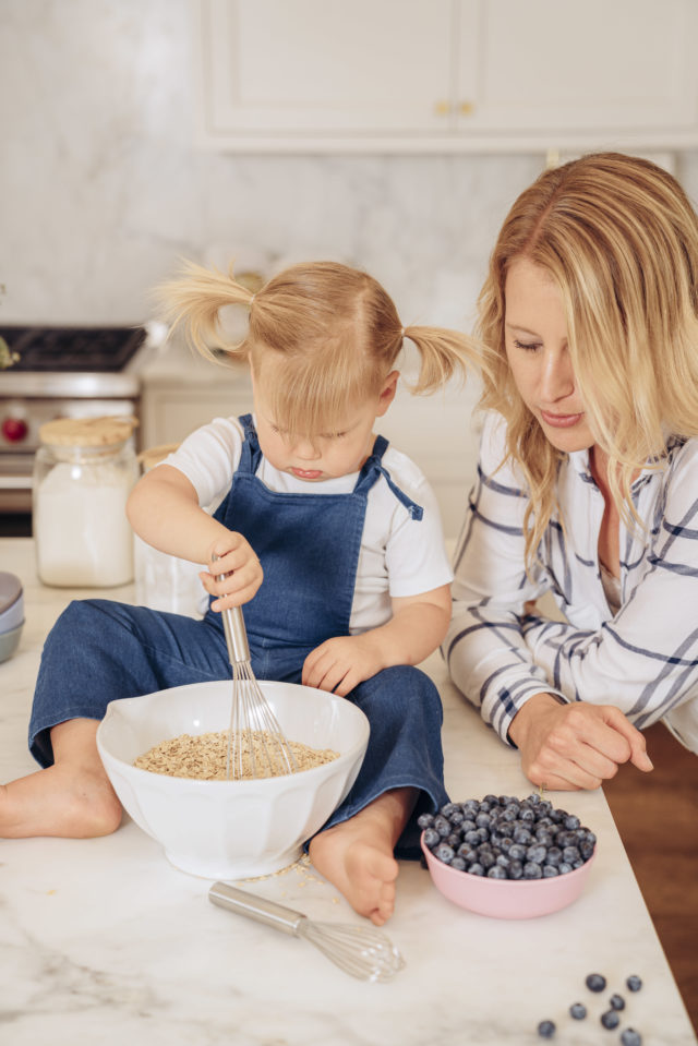 A toddler and mom baking together at the kitchen counter.