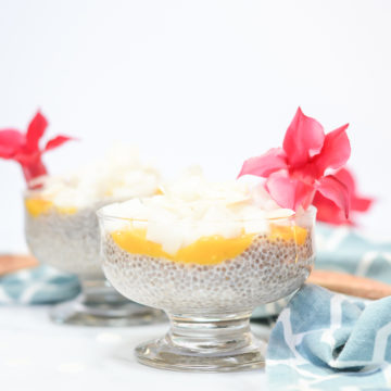 Two dishes of Coconut Passion Fruit Chia Pudding Parfait topped with pink flowers.