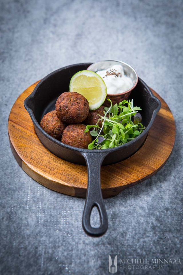 A cast iron pan of lentil falafel with lime yogurt dip.