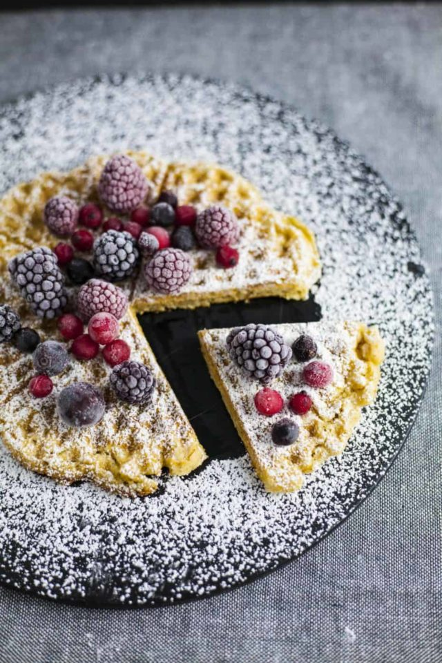 A plate of Crispy Vegan Waffles with Lentil Protein topped with berries and powdered sugar.