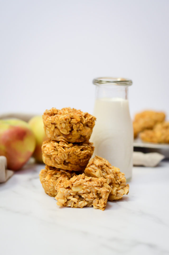 A stack of Pumpkin Apple Baked Oatmeal Cups leaning against a pitcher of milk.