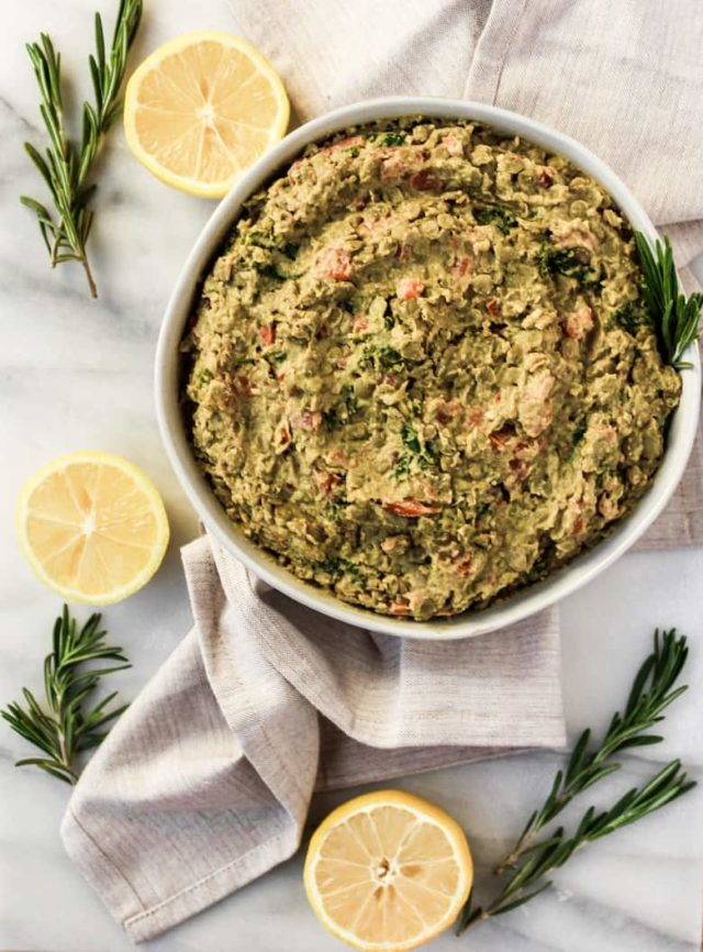 An overhead shot of a bowl of Lemon Tahini Lentil Hummus surrounded by fresh rosemary and lemons.