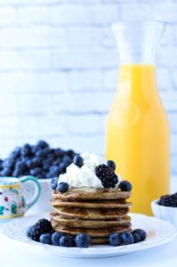A stack of Quinoa Blender Pancakes served with orange juice and blueberries.