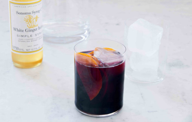 A glass of Spicy Ginger Sangria with glasses, ice and ginger simple syrup in the background.