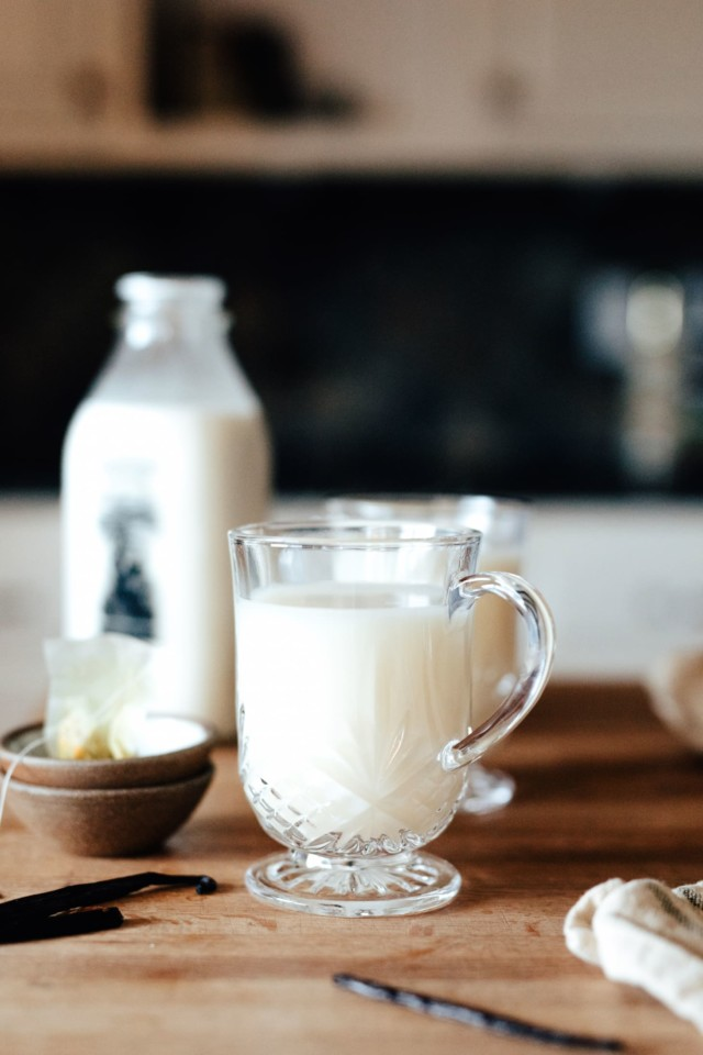 A Vanilla Bean Steamer on a tables with a jug of milk and vanilla beans in the background.