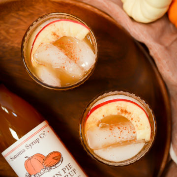An overhead shot of two glasses of Pumpkin Apple Bourbon Smash on a wooden platter.