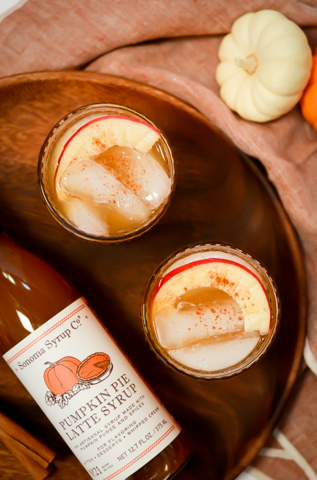 An overhead shot of two glasses of Pumpkin Apple Bourbon Smash on a wooden platter.