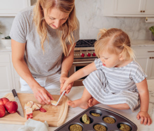 A mom and daughter slicing peaches together in the kitchen.