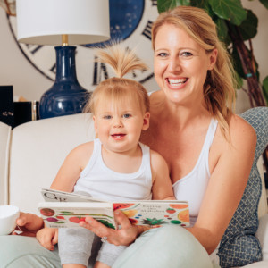 A mom and daughter smiling at the camera while sitting on the couch reading a book.