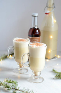 Two glasses of Winter Spiced Vanilla Eggnog amid twinkly lights.