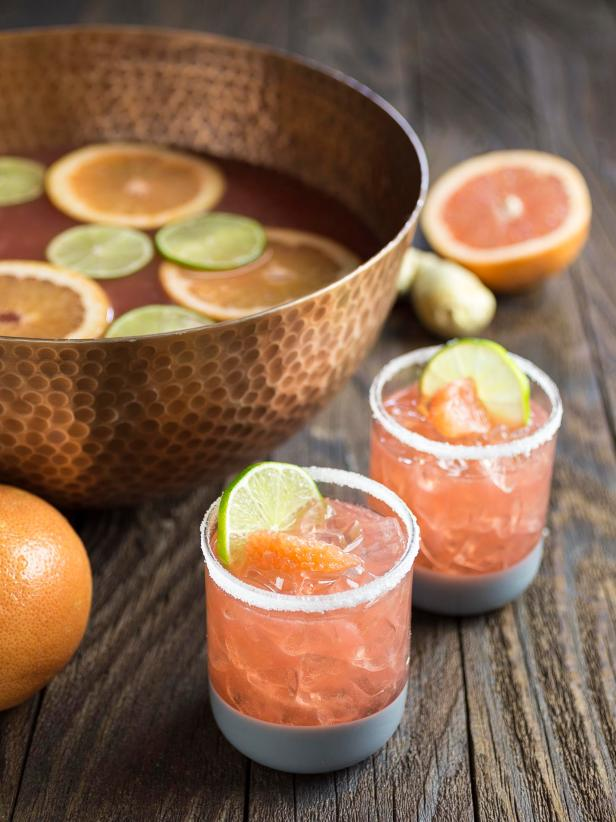 A punch bowl of Ginger Grapefruit Bourbon Sour with two filled glasses and sliced grapefruit alongside.