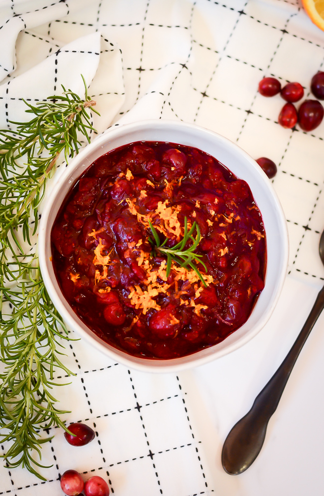 An overhead shot of a bowl of 30-minute cranberry sauce topped with orange zest and rosemary.