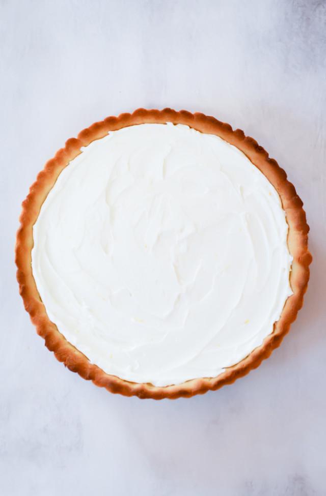 An overhead shot of an almond tart crust filled with a zesty Greek yogurt filling.