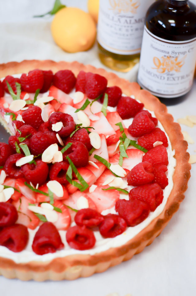 A Greek Yogurt Berry Tart with Almond Crust surrounded by bottles of almond extract and almond syrup, plus fresh lemons.