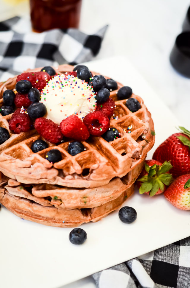 A plate of funfetti waffles topped with butter, sprinkles and fresh berries.