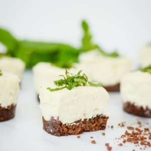 A fresh mint mini cheesecake with a bite out of it with more mini cheesecakes behind it.