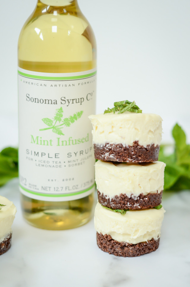 A stack of three mini fresh mint cheesecakes with a bottle of mint-infused simple syrup.