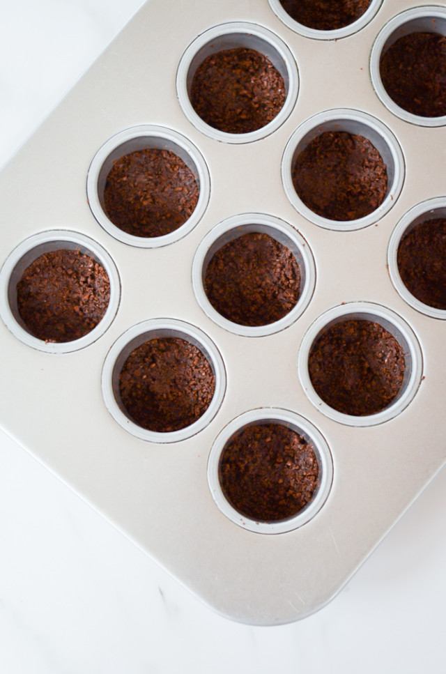 An overhead shot of a mini cheesecake pan filled with chocolate cookie crust.