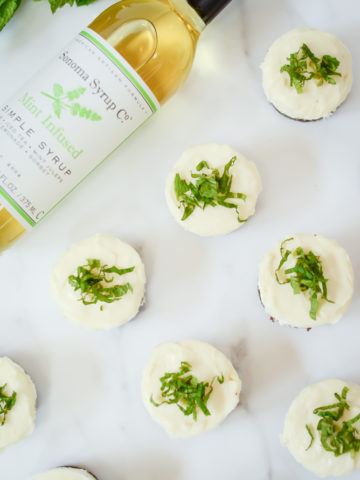 An overhead shot of a batch of Mini Fresh Mint Cheesecakes and a bottle of mint-infused simple syrup.