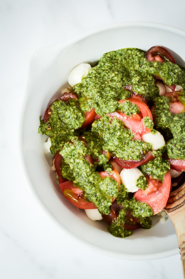 A mixing bowl full of all of the ingredients for Hazelnut Pesto Caprese Couscous.