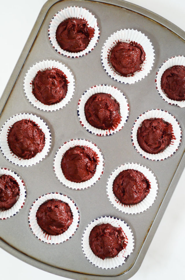 Red velvet brownie batter spread into the bottom of individual cupcake tins.