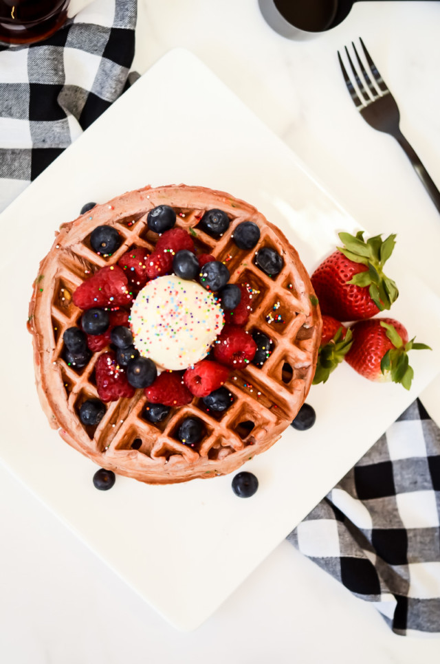 A plate of funfetti waffles with fresh berries, butter and sprinkles.