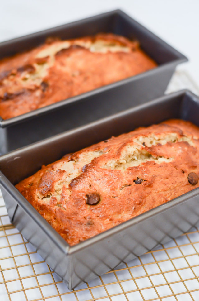 Two finished loaves of banana bread in their pans on a cooling rack.
