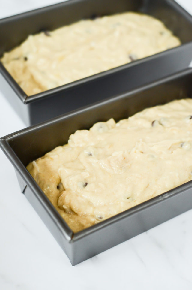 Banana bread batter divided into two loaf pans.