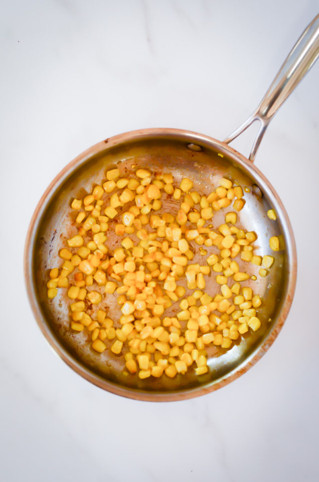 Corn kernels being sauteed in a pan.