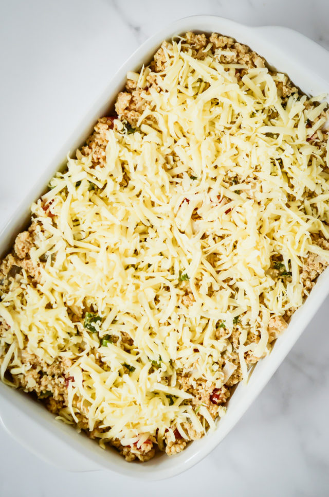 A baking dish filled with the enchilada quinoa bake mixture and topped with shredded cheese.